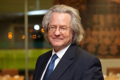 A photo of AC Grayling in a suit, smiling.