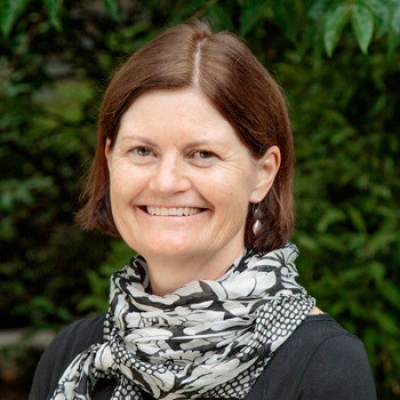 A photo of Kate O'Regan in a black blouse, smiling.