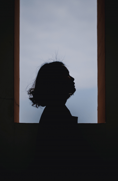 The silhouette of a woman standing in front of a window