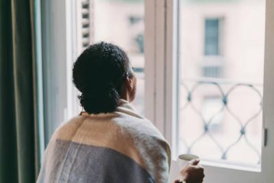 Woman in quarantine staying at home, drinking coffee, feeling depressed.