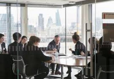 A picture of 8 people sitting around a conference table.