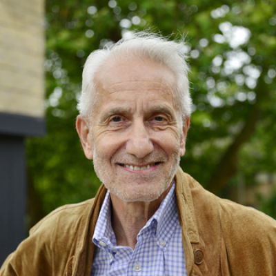 A picture of Prof Paul Craig against a green background. He is smiling and is wearing a mustard coat over a white striped shirt.