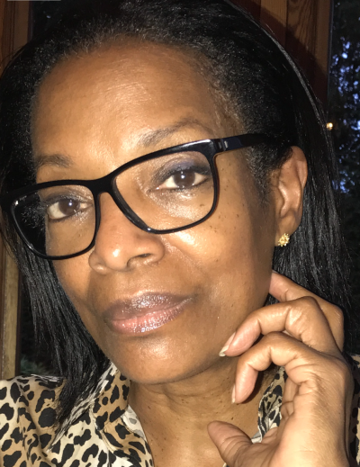 A photo of Patricia Viseur Sellers Esq, wearing black-rimmed glasses.