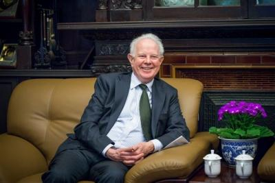 A picture of Lord Thomas sitting on a mustard sofa and smiling. There are purple flowers by the side of the sofa. Lord Thomas is dressed in a grey suit and is wearing a striped white shirt and green tie.