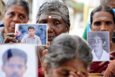 A woman in tears, holding the photo of her missing relative.