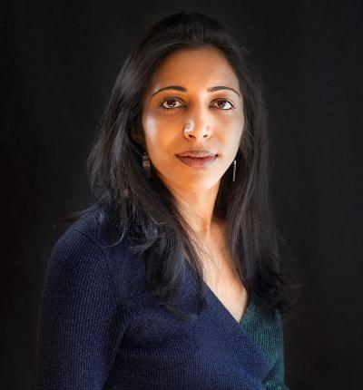 A picture of Vidhya Ramalingam in a dark blue and green jumper.