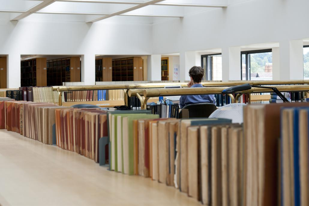 Male student sat in the library amongst rows of books