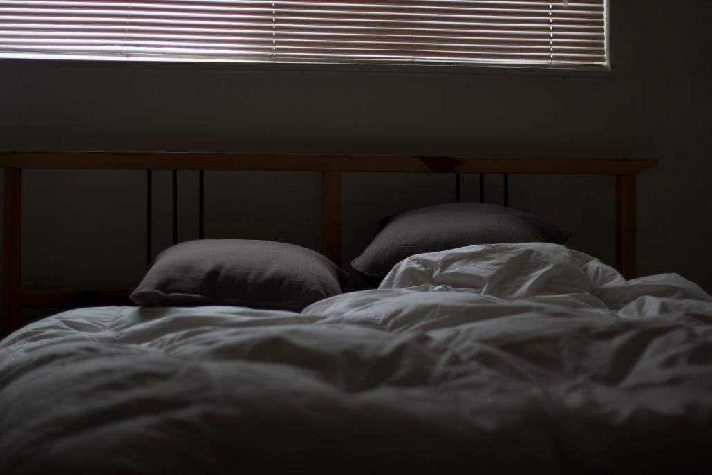 Image shows a double bed with two pillows and a set of blankets in a dimly lit bedroom
