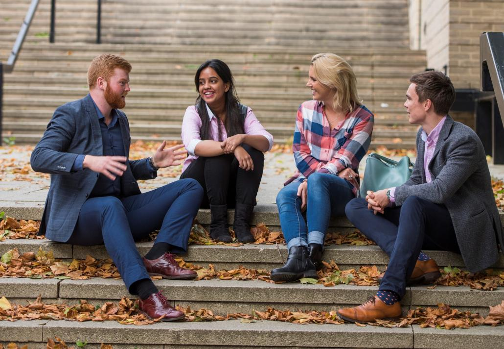 Photo of Students sat on some steps chatting