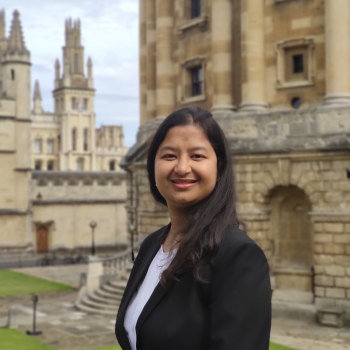 Anjali is standing on the Mound in Exeter College Fellows Garden with Radcliffe Camera in the background
