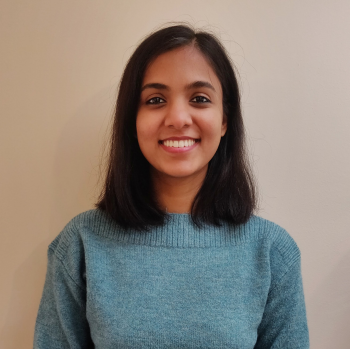 A portrait of Gayathree in a turqouise-coloured sweater, smiling.