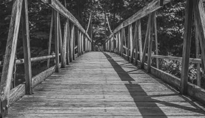 A black and white image looking across a wooden bridge.