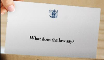 Photo of a hand holding an envelope with 'what does the law say' written on it- taken from Google Images