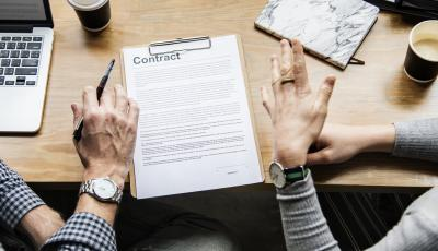 Image shows two people discussing a contract