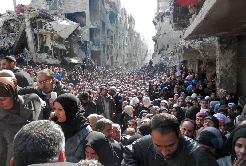 Masses of refugees wait in line to receive food aid distributed in the Yarmouk camp on Jan. 31 in Damascus, Syria. United Nation Relief and Works Agency/Getty Images